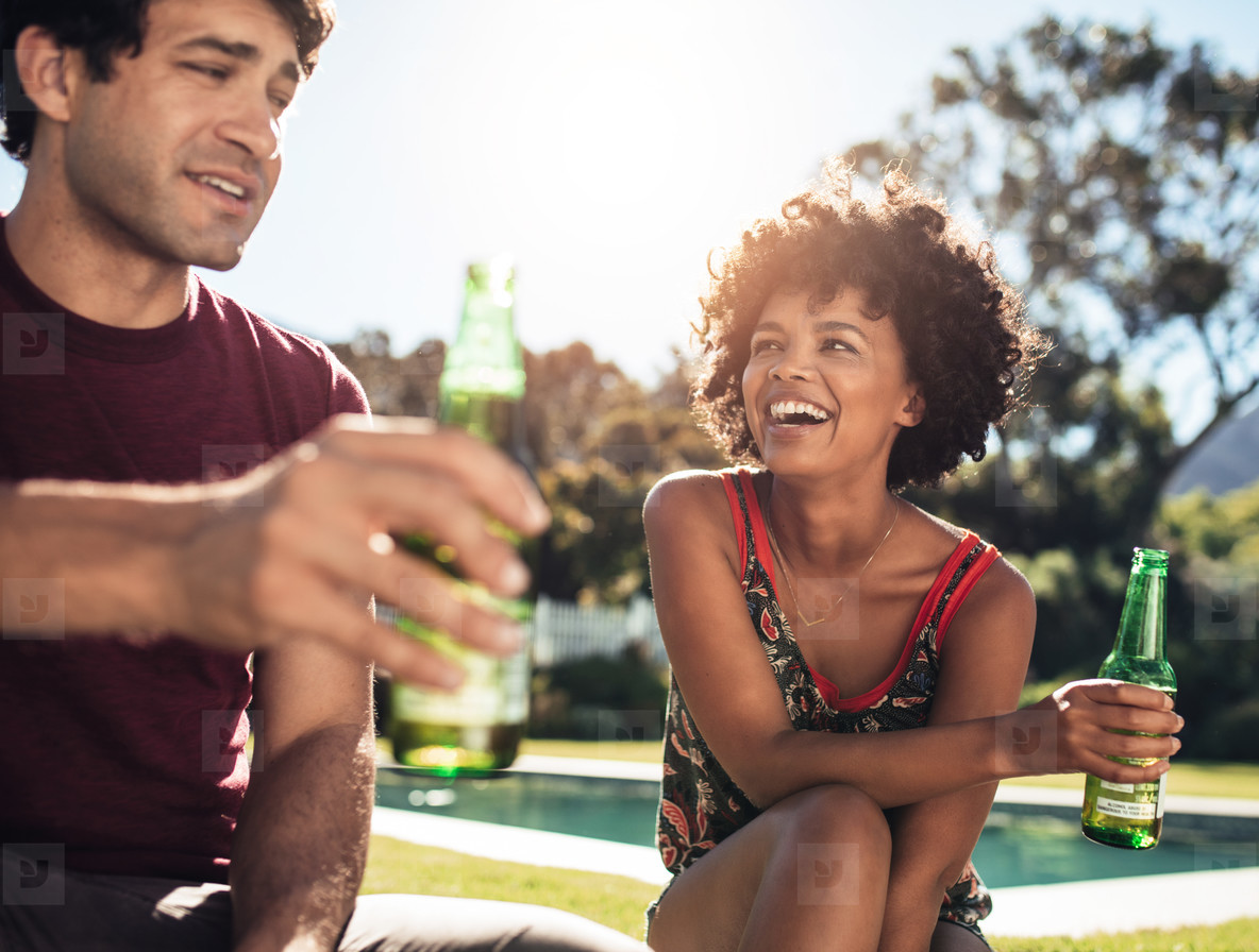 Happy young couple sitting outdoors with beers