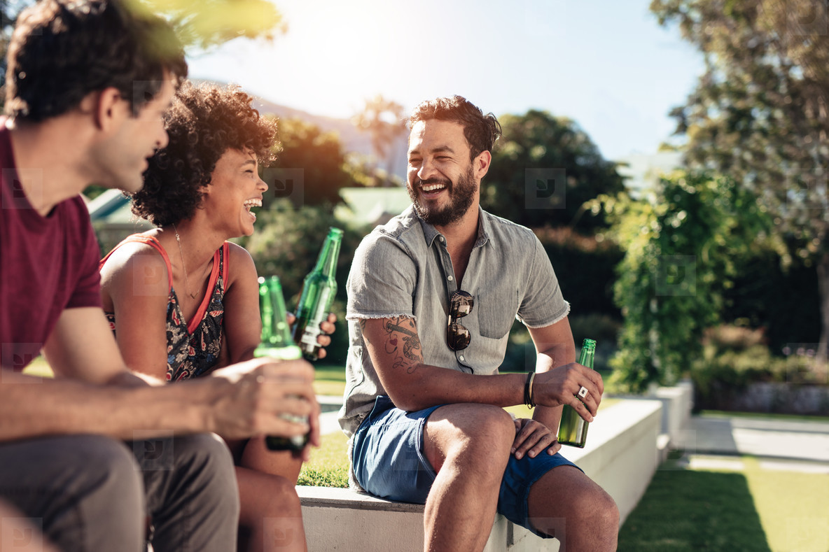 Group of friends hanging out with drinks outdoors