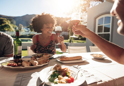 Smiling young woman toasting wine with friend