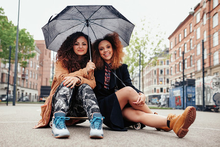 Two young friends sitting on a skateboard with an umbrella