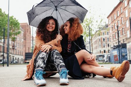Cheerful women sitting on skateboard with umbrella