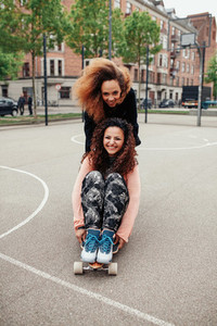 Hipster girls riding on skateboards along the road