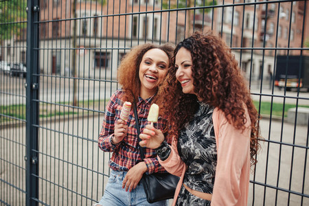 Happy women eating an ice cream outdoors