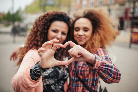 Friends making heart shape with fingers