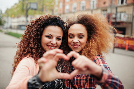 Beautiful young women making heart shape