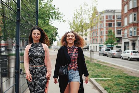 Two girlfriends walking along city street