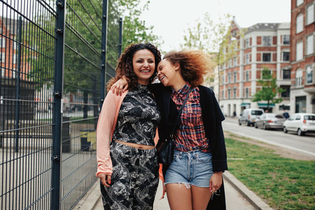 Happy young women walking along city street