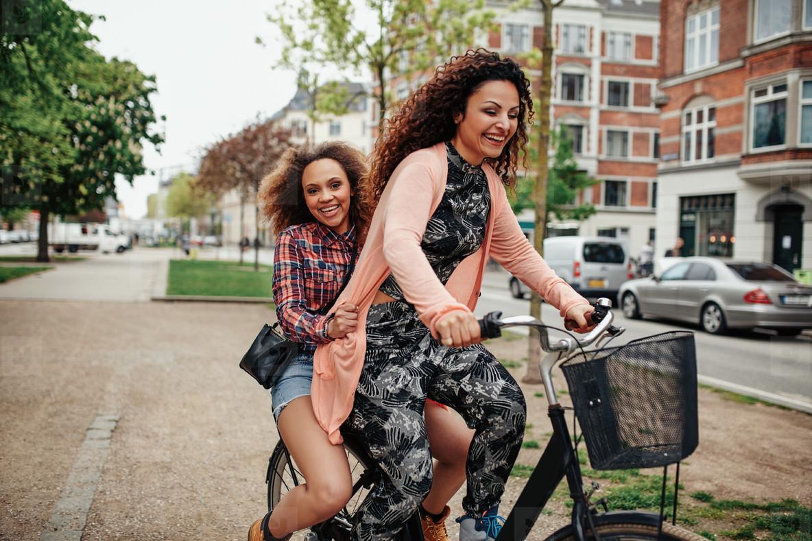Young women enjoying bicycle ride on city street