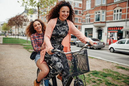 Two young girls having fun on bicycle