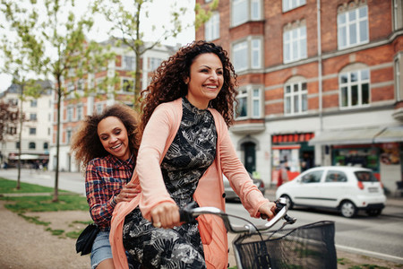 Cheerful young friends riding a bicycle in the city