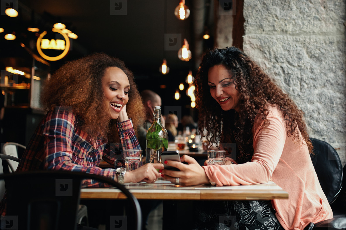 Young women sitting at cafe and using phone