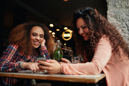Women having fun using a smart phone in cafe