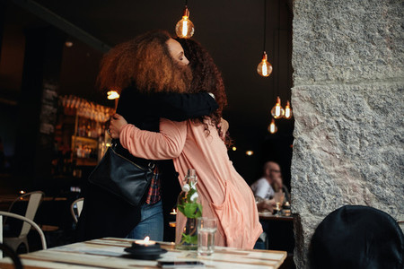 Two young women meeting at a restaurant