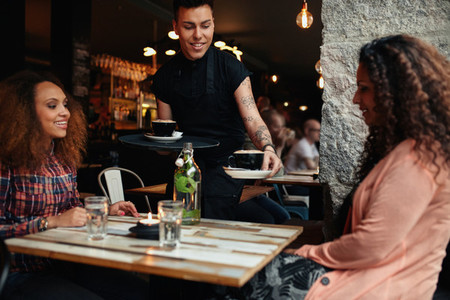 Waiter serving coffee to young women at cafe