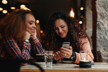Young girls sitting at cafe and using phone