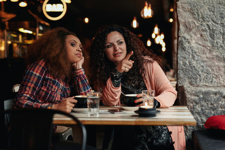 Two young women at restaurant looking away