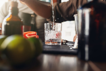 Bartender pouring drink into a glass