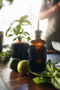 Syrup with lemons and basil leave on bar table