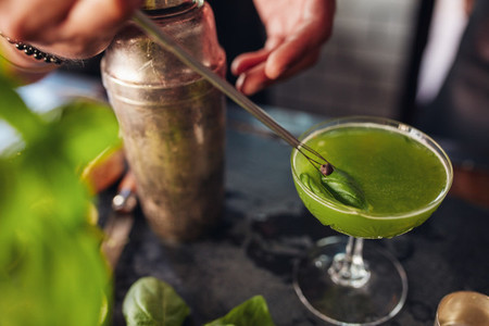 Barman hands garnishing fresh green cocktail