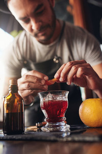 Bartender garnishing new negroni cocktail