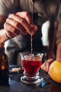 Bartender hand stirring a negroni cocktail