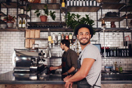 Coffee shop owner with barista working in behind