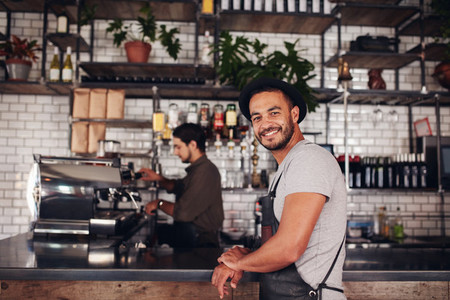 Happy young male coffee shop owner standing