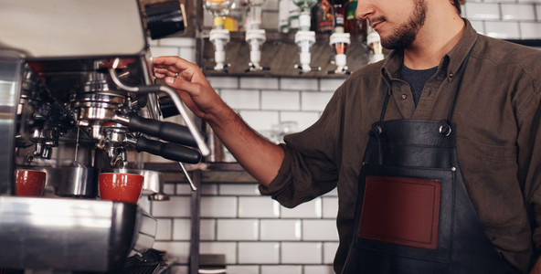 Barista using a coffee maker to make a nice cup of coffee