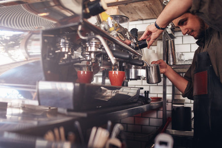 Barista using coffee maker to make a cup of coffee