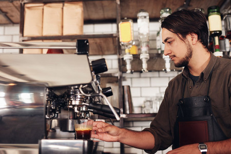 Male barista preparing espresso at coffee shop
