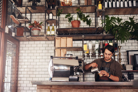 Young male barista making a cup of coffee