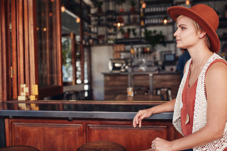 Beautiful young woman sitting alone at bar counter