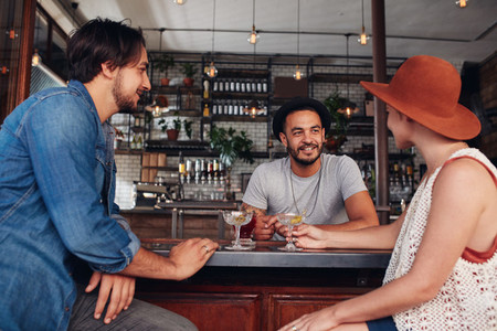 Three young friends at cafe having drinks together