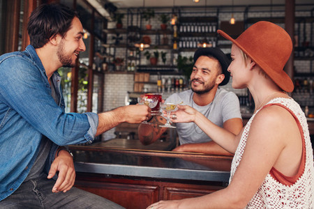 Young friends toasting drinks at cafe