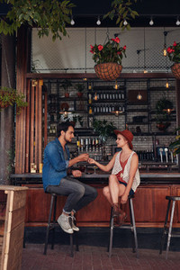 Couple sharing cigarette at coffee shop