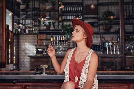 Attractive young woman smoking in a bar