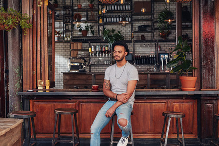 Upset young man sitting alone at a cafe counter