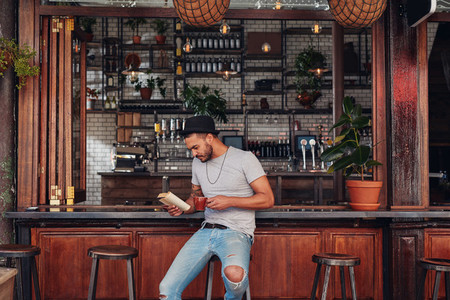 Modern young man reading a book in cafe