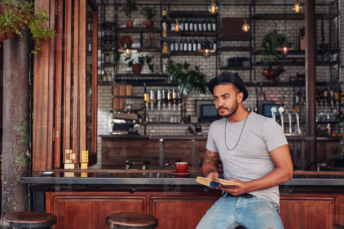 Trendy young male sitting at a cafe counter with a book