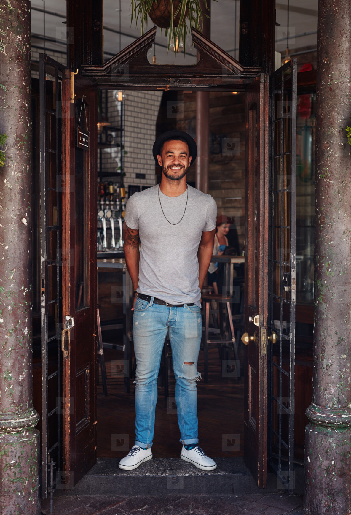 Stylish young man standing at the front door of coffee shop