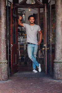 Modern young guy standing at the entrance of a coffee shop