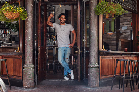 Smiling young man standing at the door of a cafe