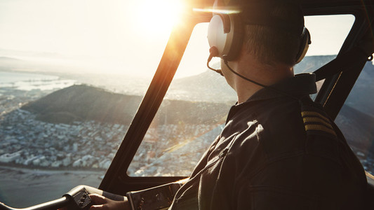 Pilot flying a helicopter and looking outside the window