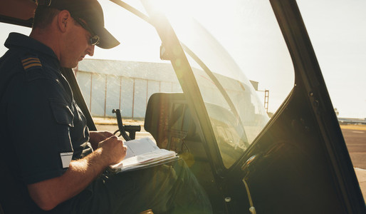 Pilot checking the flight manual before a take off