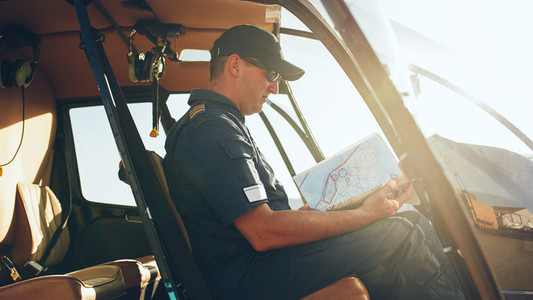 Helicopter pilot reading flight map