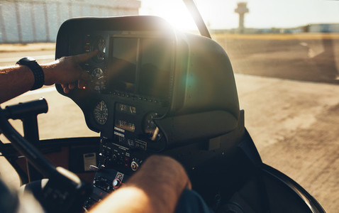 Helicopter pilot checking gauges on the instrument panel