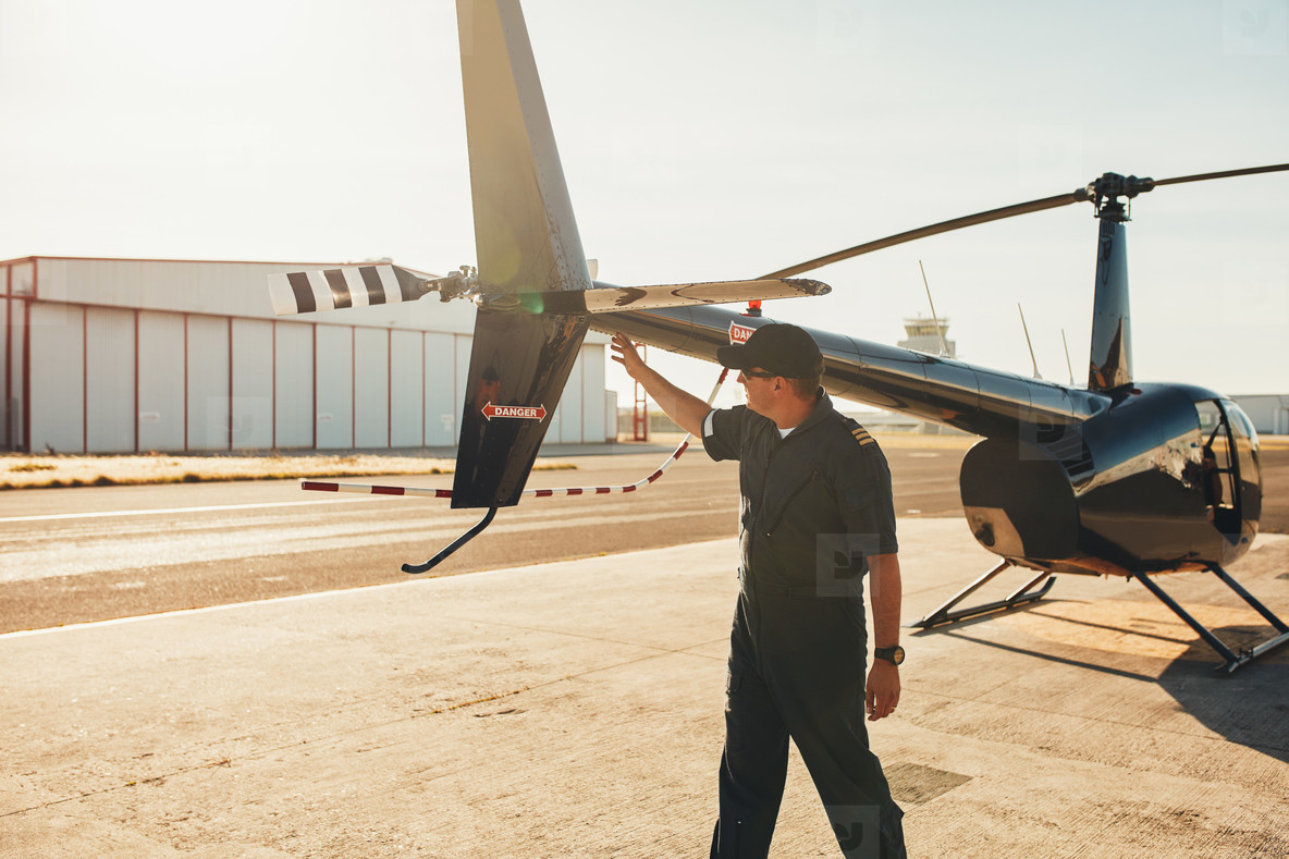 Pilot checking helicopter tail during preflight check