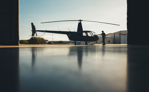 Silhouette of helicopter in the hangar with a pilot