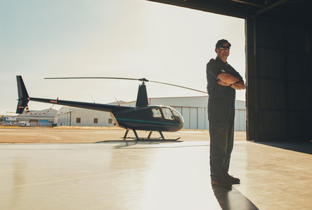Confident pilot standing in airplane hangar