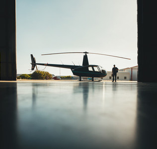Silhouette of helicopter and a pilot in hangar